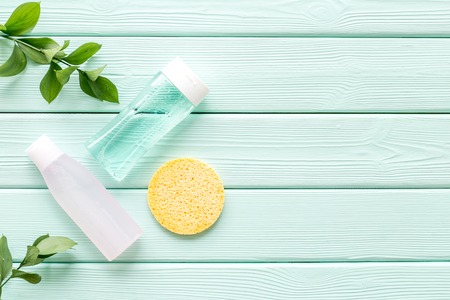 Organic cosmetics for face clearing with sponge, facial tonic, mycelial water on mint green background top view mockup