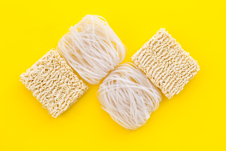 Rice vermicelli, noodles to cook Chinese and Japanese food design on yellow background top view copy space Imagens