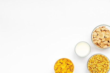 Various corn cereals in bowls and milk on white background top view copyspace