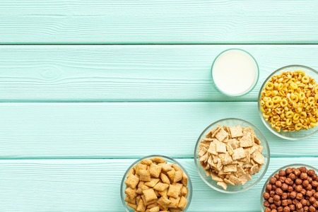 cereals, oatflakes and cornflakes with milk for healthy breakfast on mint wooden background top view mock up