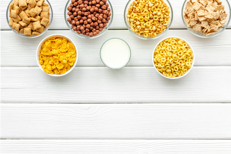 Various corn cereals in bowls and milk on white wooden background top view copyspace