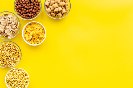 cereals, oatflakes and cornflakes for healthy breakfast on yellow background top view mock up