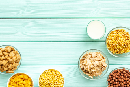 Energy snacks. Various corn cereals in bowls and milk on mint wooden background top view copyspace