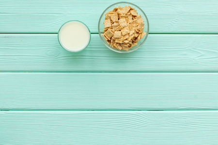 cereals, oatflakes and cornflakes with milk for healthy breakfast on mint wooden table background top view mock up 版權商用圖片