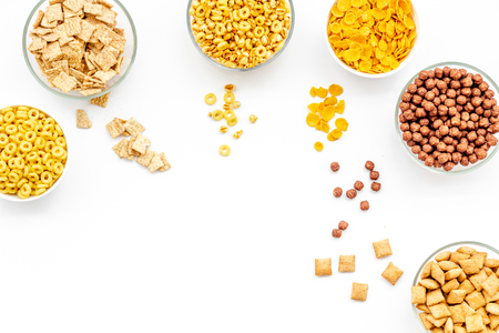 Energy snacks. Various corn cereals in bowls on white background top view copyspace