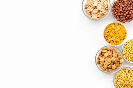 Various corn cereals in bowls on white  top view copyspace Imagens