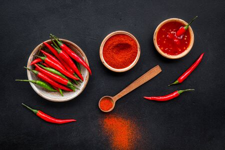 Fresh red chilli pepper and dry powder as food ingredient on dark table  top view