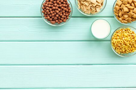 Various corn cereals in bowls and milk on mint wooden  top view copyspace