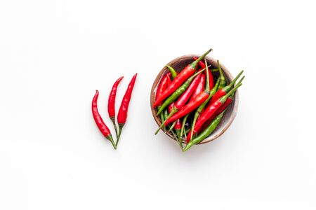 Fresh red and green chilli pepper as food ingredient on white table Imagens