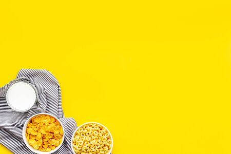 Various corn cereals in bowls and milk on yellow  top view copyspace