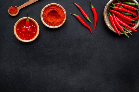 Cooking hot food with chilli pepper on black table  top view copy space
