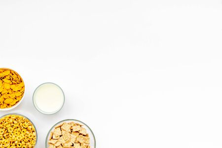 Cereals, oat flakes and cornflakes with milk for healthy breakfast on white  top view mock up Imagens