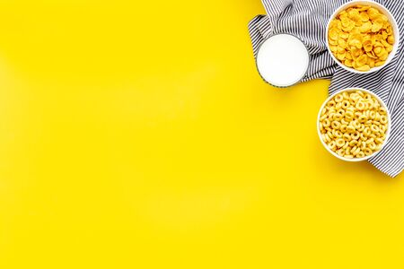 Cereals and flakes from corn and oat on yellow  top view mockup Imagens
