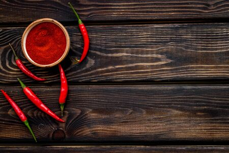 Fresh red chilli pepper and dry powder as food ingredient on wooden table  top view mockup