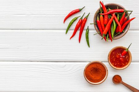 Fresh and powdered red and green chilli pepper pattern on white wooden table  top view space for text
