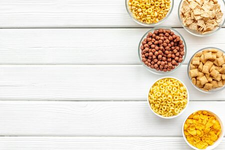 Various corn cereals in bowls on white wooden  top view copyspace