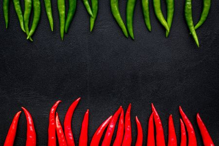 Cooking hot food with chilli pepper on black table   top view copy space Imagens