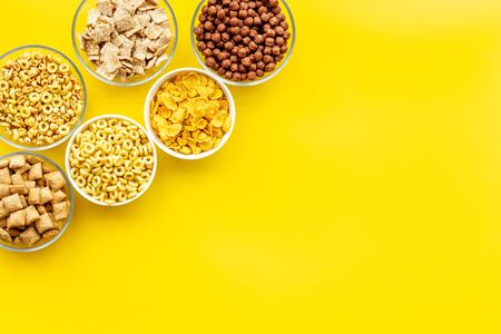 Various corn cereals in bowls on yellow  top view copyspace Imagens