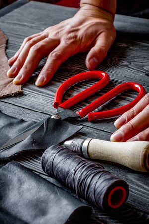 Work in leather shop on dark wooden  close up with hands Banco de Imagens - 124961761