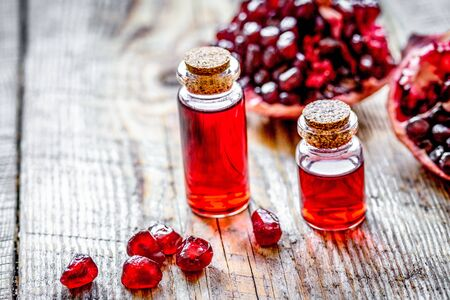 Sliced pomegranate and extract in glass on wooden close up