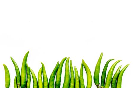 Food ingredients. Fresh green chilli pepper pattern on white table  top view space for text