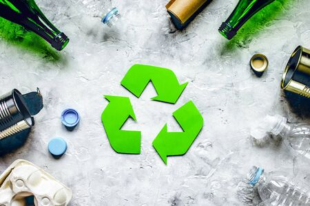 Eco concept with recycling symbol and garbage on stone table  top view