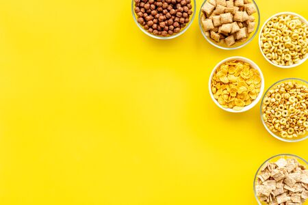 Various taste and shape. Cereals and flakes from corn and oat on yellow