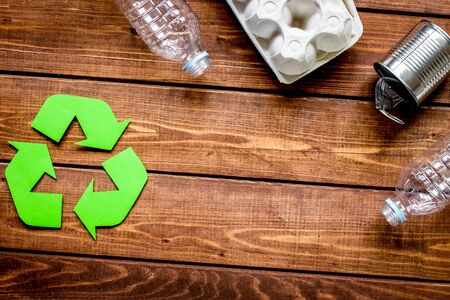 Eco concept with recycling symbol and garbage on wooden table