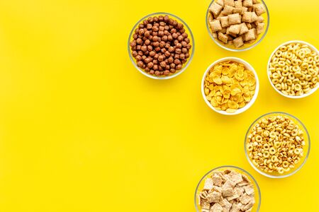 Various corn cereals in bowls on yellow background top view copyspace 版權商用圖片