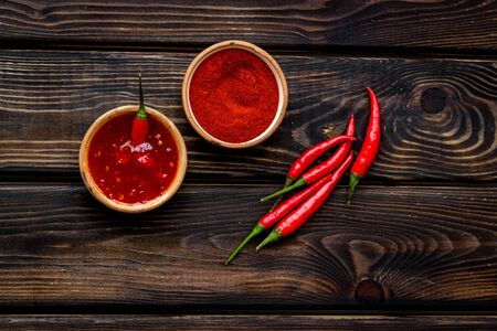 Cooking hot food with chilli pepper on wooden table