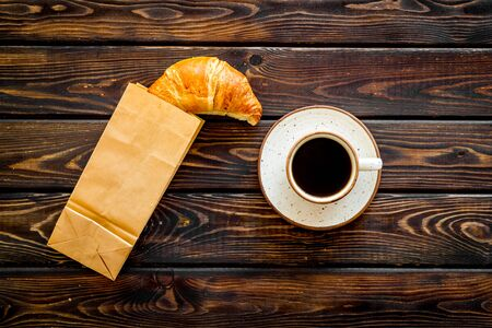 Fresh pastry. Breakfast with croissant in paper bag and cup of coffee on wooden Фото со стока