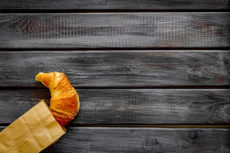 Fresh pastry with croissant in paper bag on wooden background top view mockup