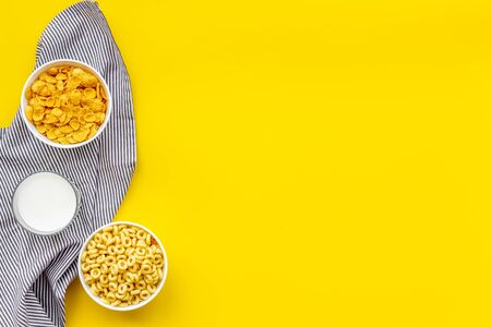Various corn cereals in bowls and milk on yellow background top view copyspace