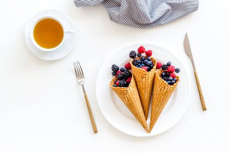 Light breakfast with fresh berries in waffle cones and cup of tea on served white table background top view