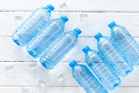 Plastic bottles with pure water and ice on white wooden background top view
