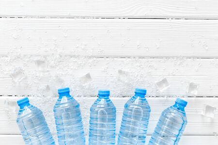 Pure frozen water in plastic bottles on white wooden background top view copyspace Imagens