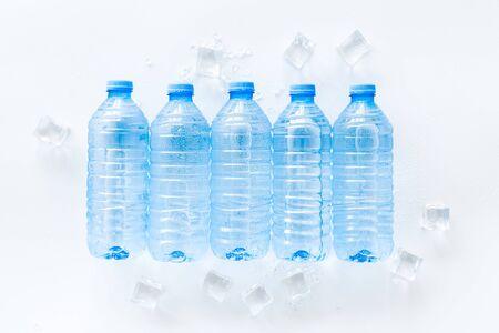 Botellas de plástico vacías para agua pura con cubitos de hielo sobre fondo blanco vista superior