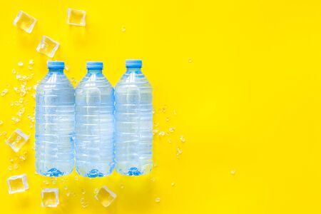 Pure frozen water in plastic bottles on yellow background top view copyspace