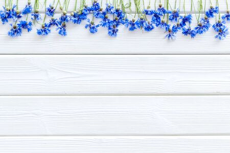 Field flowers design with blue cornflowers on white wooden  top view mockup