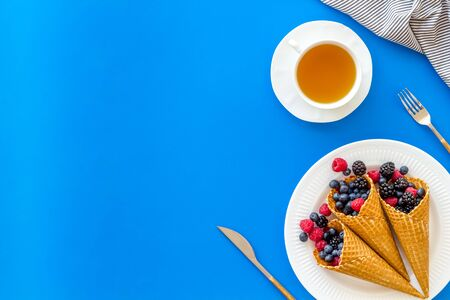 Light breakfast with fresh berries in waffle cones and cup of tea on served blue table  top view mockup