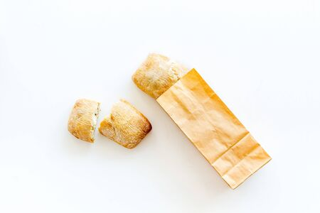 Fresh baguette and paper bag for bakery on white  top view Banque d'images