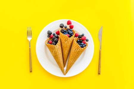Light breakfast with fresh berries in waffle cones and tableware on served yellow table background top view