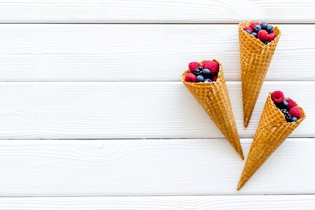 Fresh berries in waffle cones on white wooden background top view mock up