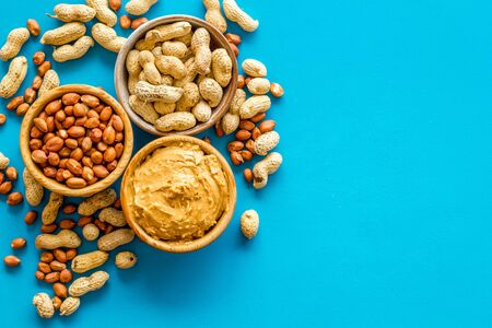 Vegan breakfast. Make peanut butter with nuts and paste in bowl on blue background top view copyspace