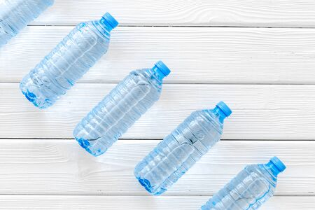 Pure water in plastic bottles on white wooden background top view
