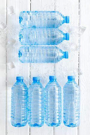 empty plastic bottles for pure water with ice cubes on white wooden background top view