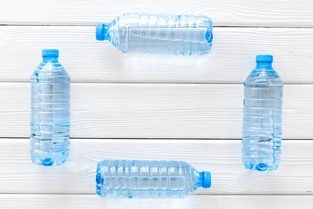 Plastic bottles with pure water frame on white wooden background top view space for text