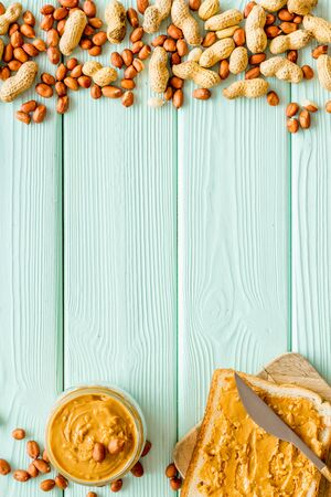 Make sandwiches with peanut butter in glass bowl on mint green wooden background top view copyspace