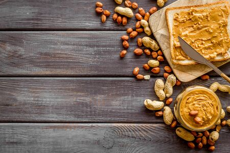 Make sandwiches with peanut butter in glass bowl on wooden background top view copyspace Imagens