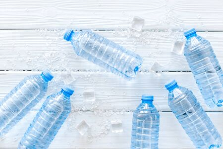 empty plastic bottles for pure water with ice cubes on white wooden background top view pattern